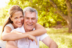 Senior man embraced by his adult daughter, outdoors Stock Images
