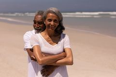 Senior man embracing senior woman on beach. Front view of senior man embracing senior woman on beach in the sunshine royalty free stock photo
