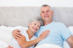 Senior man embracing woman in bed Royalty Free Stock Images