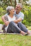 Senior man embracing woman from behind at park Royalty Free Stock Images