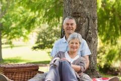 Senior man embracing woman from behind at park Royalty Free Stock Image