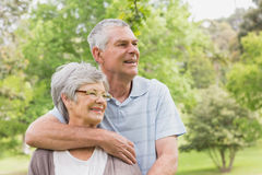 Senior man embracing woman from behind at park Stock Image