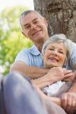 Senior man embracing woman from behind at park Royalty Free Stock Photos