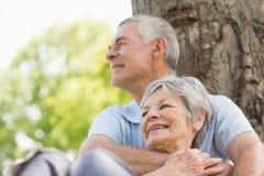 Senior man embracing woman from behind at park Stock Image