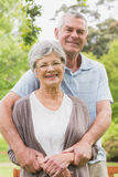 Senior man embracing woman from behind at the park Stock Photo