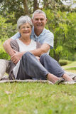 Senior man embracing woman from behind at park Royalty Free Stock Photography