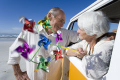 Senior man embracing woman with pinwheel through window of camper van on beach, smiling Stock Photography