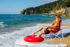 Senior man enjoying at the beach. Senior man sitting in chair with toys at the summer beach Stock Photography
