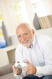Senior man enjoying computer game. Laughing, sitting at home Royalty Free Stock Photo