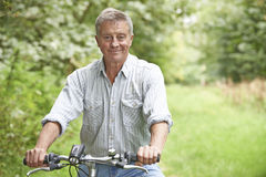 Senior Man Enjoying Cycle Ride In The Countryside Royalty Free Stock Photo