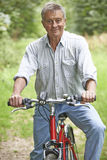 Senior Man Enjoying Cycle Ride In The Countryside Stock Photo