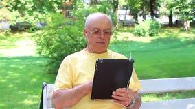 Senior man enjoying music on his digital tablet pc stock video footage