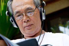 Senior man enjoying music on his tablet Royalty Free Stock Image