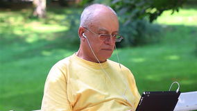 Senior man enjoying music on his tablet pc stock video
