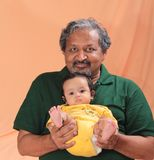Senior man enjoying time with grand daughter. Indian elderly grand father holds infant baby grand daughter in arms and playing happily royalty free stock photography