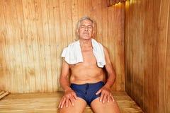 Senior man enjoys heat in the sauna. Senior man enjoys heat in the spa sauna with his eyes closed stock photo