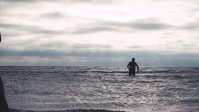 Senior man enters sea waves. In cloudy weather stock video