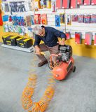 Senior Man Examining Air Compressor In Shop. Full length of senior man examining air compressor in hardware shop Royalty Free Stock Image