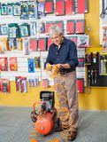 Senior Man Examining Air Compressor In Store. Full length of senior man examining air compressor in hardware store Royalty Free Stock Images