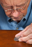 Senior man examining half dollar Stock Image
