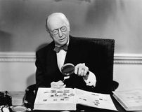 Senior man examining a postage stamp with a magnifying glass Royalty Free Stock Images
