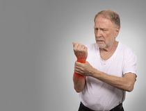Senior man in excruciating hand ache painful wrist arthritis Royalty Free Stock Image
