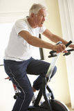Senior Man On Exercise Bike Stock Photo