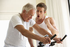 Senior Man On Exercise Bike With Trainer Stock Photo