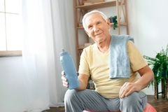 Senior man exercise at home sitting on exercise ball rest drinking water. Senior man exercise indoors sitting on exercise ball drinking water rest looking camera Royalty Free Stock Image