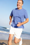 Senior Man Exercising On Beach Stock Photo
