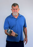 Senior Man Exercising with Dumbbell. An senior man exercises with a chrome dumbbell Royalty Free Stock Photography
