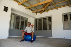Senior man exercising with dumbbells on exercise ball in the porch Royalty Free Stock Photography