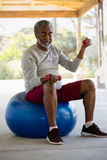 Senior man exercising with dumbbells on exercise ball in the porch Royalty Free Stock Images