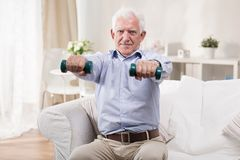 Senior man exercising with dumbbells Stock Images