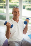 Senior man exercising with dumbells at home. Happy senior man exercising with dumbells at home Stock Photo