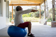 Senior man exercising on exercise ball in the porch Stock Images