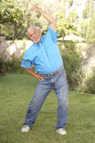 Senior Man Exercising In Garden Stock Images