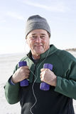 Senior man exercising with hand weights on beach Royalty Free Stock Photo