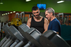 Senior man exercising on jogging machine. Senior men exercising on jogging machine in gym with assistance of personal trainer. Healthy lifestyle, fitness concept stock photo