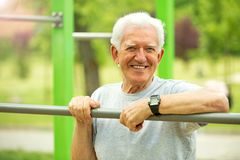Senior man exercising at outdoor gym Royalty Free Stock Photography