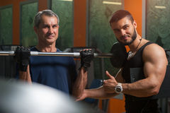 Senior man exercising with personal trainer in gym. Senior caucasian men doing biceps exercise with barbell with personal trainer. Male adult exercising with stock photos