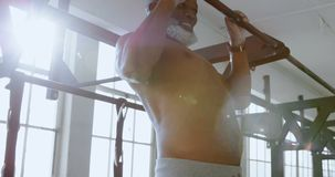 Senior man exercising pull up on a pull up bar in the fitness studio 4k