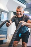 Senior man exercising with ropes at the gym. Physical activity and healthy lifestyle royalty free stock image