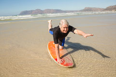 Senior man exercising on surfboard at shore Stock Images