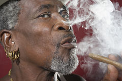 Senior Man Exhaling Cigar Smoke Royalty Free Stock Image
