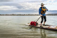 Expedition stand up paddleboard on lake. Senior man on expedition stand up paddleboard with a large waterprood duffel on deck, a lake in Colorado Royalty Free Stock Photos