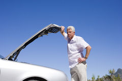 Senior man experiencing car trouble, looking at engine, leaning against open bonnet, thinking Stock Photos