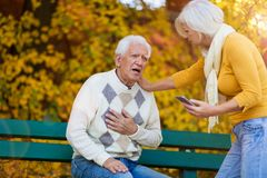 Senior man experiencing chest pain while senior woman is doing the emergency call royalty free stock photos