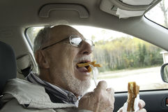 Senior man with expressive face eating  fast foods Royalty Free Stock Photography