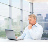 Senior man in eyeglasses with laptop at office Royalty Free Stock Photos